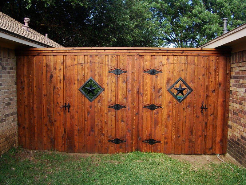 ecofencing company - woode fence with two decorated doors shared by two neighbors